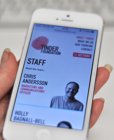 Picture of a hand holding an iPhone with responsive view of the Tinder Foundation website